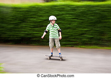young boy on his skate board - young boy is riding...