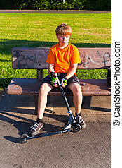 boy sitting on a bench with his scooter