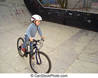 joung boy with his mountainbike trains BMX tricks in the...