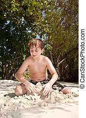 happy young boy is digging in the sand of the beach and...