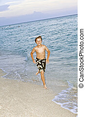 boy is jogging at the beautiful beach - young boy is jogging...