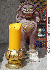 Stone lion and big yellow candle near temple in Wat Muang...