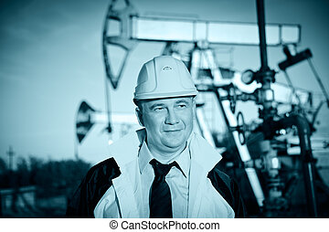 Worker in an Oil field - Oil worker in uniform and helmet on...