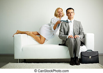 Seduction - Photo of serious man sitting on sofa with...