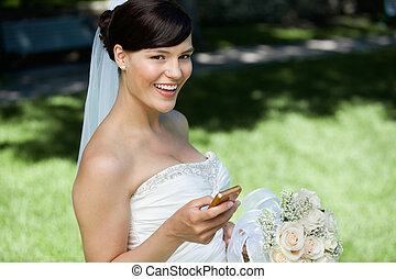 Bride Using Cell Phone - Portrait of happy bride holding...