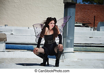 Faery on Roof - Annoyed fairy squats outdoors in black...