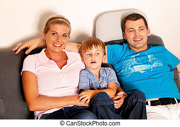 family watching television - a family is sitting in the...