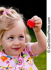 child eating a strawberry in the garden - small child eating...