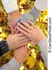 Hands of best friends together outdoor. Autumn