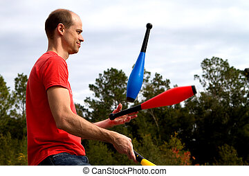 Juggling Man - Man tosses and juggles pins in the air at a...