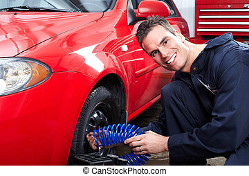 Auto mechanic changing a tire. - Professional auto mechanic...