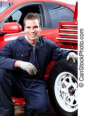 Auto mechanic changing tire. - Professional auto mechanic...