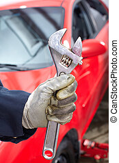 Hand with wrench. Auto mechanic.