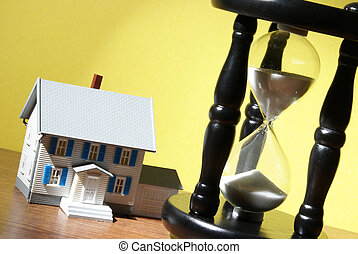 Real Estate Concept - A model house and hourglass come...