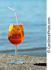 aperol spritz - a glass aperol spritz stands by the water