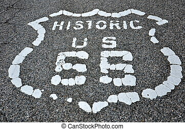 Route 66 road marker cracked and worn painted on pavement