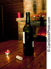 Wine bottle standing on table before fireplace - Wine bottle...