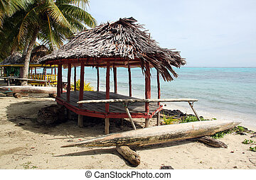 Huts and boat on the sand beach in Savaii, Samoa
