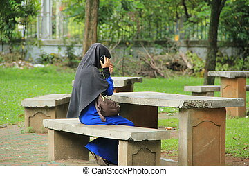 Indonesian girl - Indonesian moslim girl with mobile phone