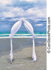 Wedding archway arranged on the sand in preparation for a...
