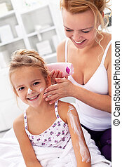 Body care - woman and little girl applying cream
