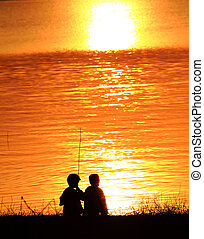 Silhouettes of two children playing along the river