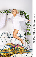 lovely girl jumping on the bed in studio