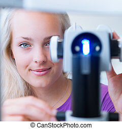 optometry concept - pretty, young female patient having her...