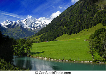 Alpine lake - Alpine peaks covered by snow and a beautiful...