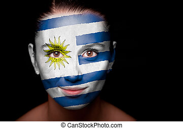 Portrait of a woman with the flag of the Uruguay painted on...