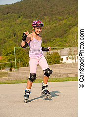 Cute young girl rollerskates on a playground
