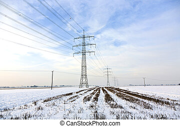 electrical tower in wintertime with snow covered fields