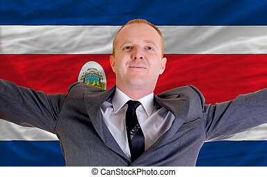 joyful investor spreading arms after good business investment in costarica, in front of flag
