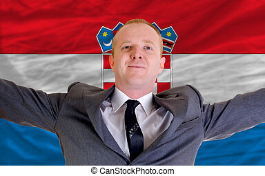 joyful investor spreading arms after good business investment in croatia, in front of flag
