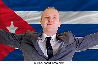 joyful investor spreading arms after good business investment in cuba, in front of flag