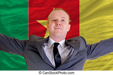 joyful investor spreading arms after good business investment in cameroon, in front of flag