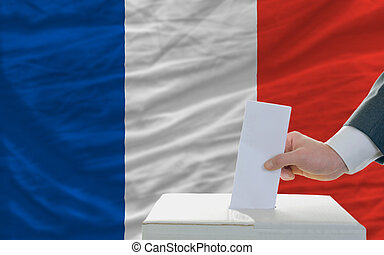 man voting on elections in france - man putting ballot in a...