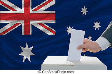 man voting on elections in australia - man putting ballot in...