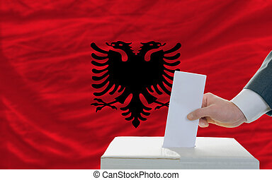 man voting on elections in albania - man putting ballot in a...