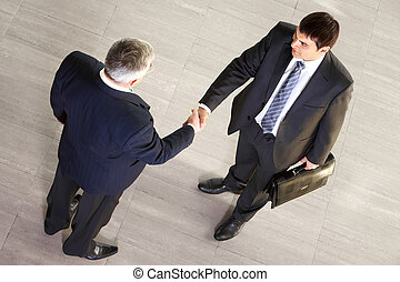 Business agreement - Over view of two businessmen concluding...