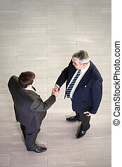 Business negotiations - Over view of two businessmen shaking...