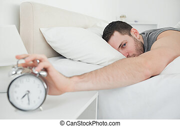 Attractive man being awakened by an alarm clock