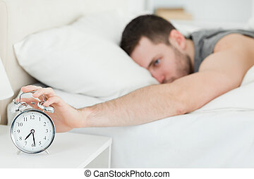 Brown-haired man being awakened by an alarm clock