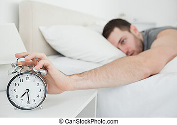 Young man being awakened by an alarm clock