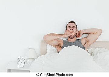 Tired man yawning while waking up in his bedroom