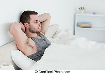 Tired man waking up in his bedroom