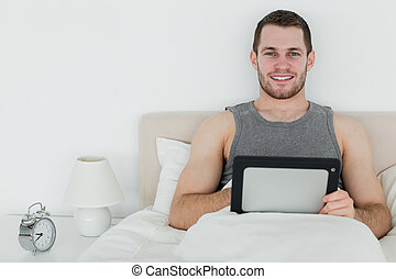 Calm man using a tablet computer in his bedroom