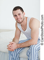 Portrait of a smiling young man sitting on his bed while...