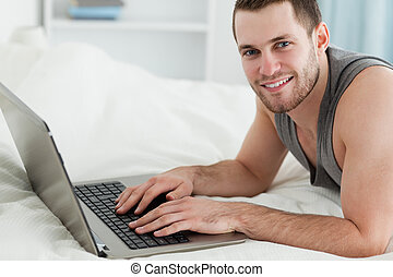 Handsome man using a laptop while lying on his belly