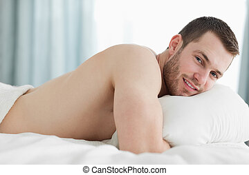 Calm man lying on his belly in his bedroom